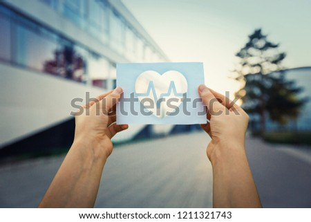 Close up of woman hands holding a paper sheet with the heart beating symbol inside, over hospital building background. Healthcare and medicine concept.