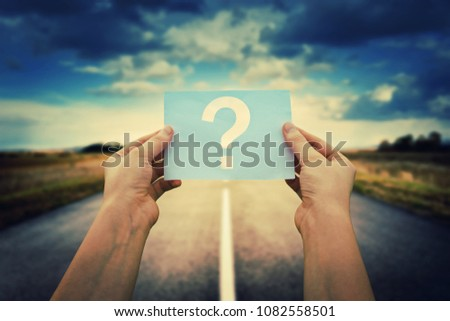 Close up of woman hands holding a paper sheet with the question mark inside, over asphalt road background. Lost people, business confusion concept, choosing the correct way.