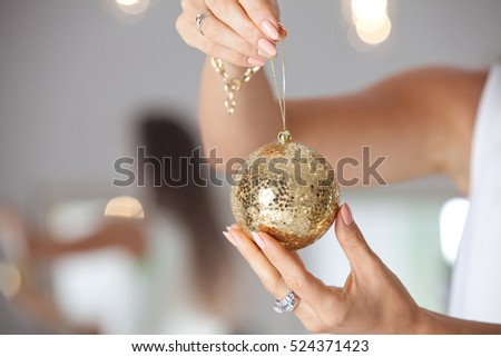 Close up of woman hands holding christmas goold ball. Decoration, holidays and people concept. #524371423
