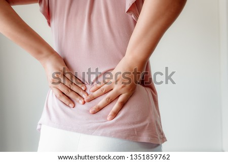 Close-Up of Woman Hands is Massaging Her Waist on Isolated Gray Background, Young Adult having Backache After Home Work. Healthcare and Medicine Concept.
