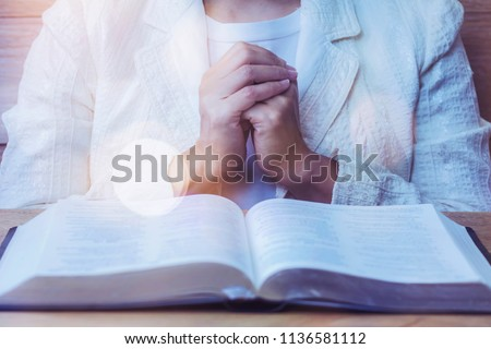 close up of woman hands praying to God while reading bible on wooden table  in morning devotion, Christian   #1136581112