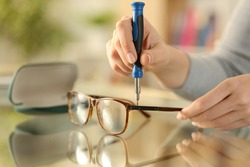 Close up of woman hands tightening screw on glasses with screwdriver on a desk at home