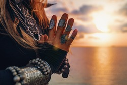 close up of woman hands. tribal style woman on the beach at sunset