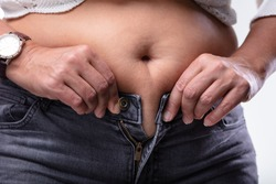 Close-up Of Woman Hands Unable To Close The Pants Due To Gaining Fat On Hips.
