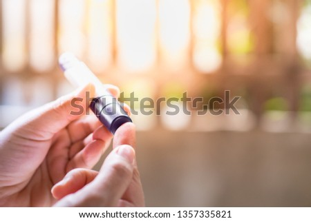 Close up of woman hands using lancet on finger to check blood sugar level by Glucose meter in the morning. Medicine, diabetes, glycemia, health care concept.