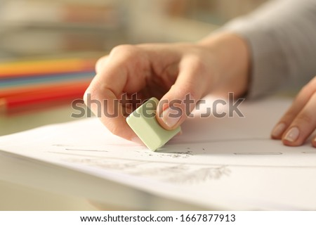 Photo of  Close up of woman hands using rubber erasing pencil drawing on a desk at home