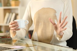Close up of woman hands with spilled coffee over her shirt holding coffee cup sitting on a desk at home