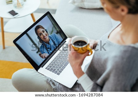 Close-up of woman having video call over laptop with her doctor while drinking coffee at home.