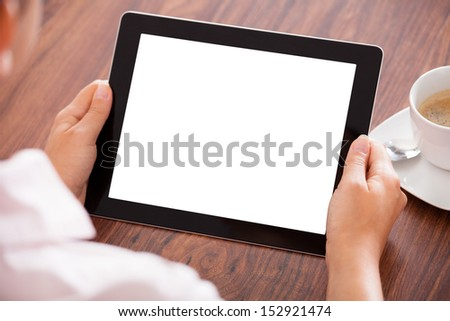 Close-up Of Woman Holding Digital Tablet In Front Of Coffee Cup