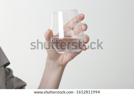 Close up of woman holding glass of water