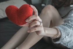 Close up of woman holding heart shape with an elegant engagement diamond ring on the finger. love and wedding concept.