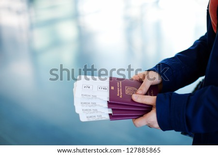 Close up of woman holding passports and boarding passport at airport