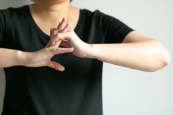 Close-up of woman in black T-shirt is cracking her knuckles; after working hard that using hand and fingers; or gesturing like ready for doing something; concept of health care and medical.