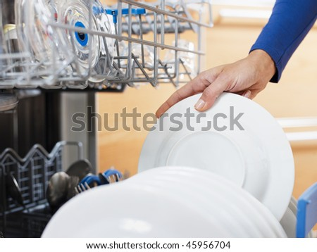 close up of woman in kitchen using dishwasher