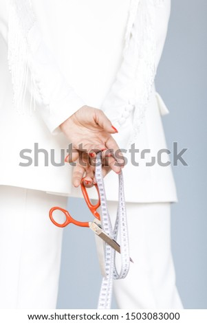close up of woman in white  fashion suit holding scissors and centimeter tape behind her back. Fashion designer of closes concept. Fashion closes designer with scissors and centimeter tape
