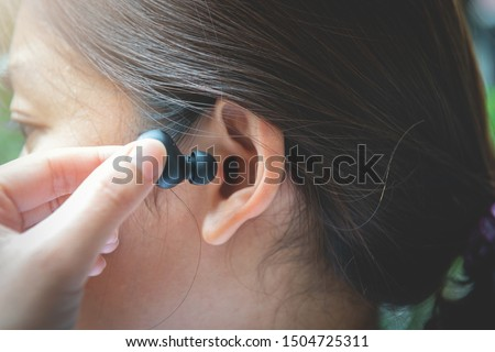 Close up of woman is using the black true wireless earbuds by hand to put in ear and control Stock photo ©