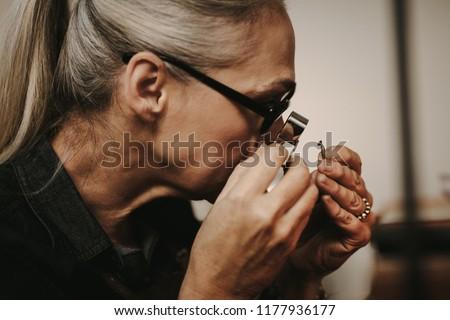 Close up of woman jeweler examining diamond through loupe at workshop. close-up Senior female jeweler looking at diamond through magnifying loupe.