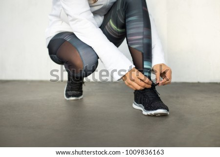 Close up of woman lacing sports shoes before running and exercising.