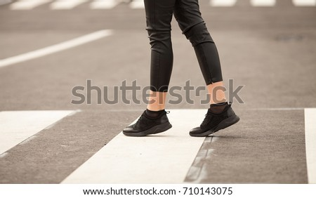 Close up of woman legs walking on crosswalk. The woman is wearing black sneakers. #710143075