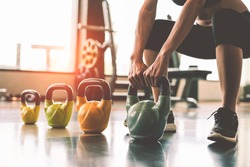 Close up of woman lifting kettlebell like dumbbells in fitness sport club gym training center with sport equipment near window background. Lifestyles and workout exercise for bodybuilding and healthy