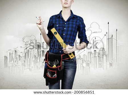 Close up of woman mechanic with ruler in hand against city background
