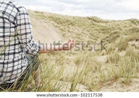 close up of woman meditating on beach in sand dunes - stock photo