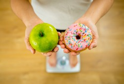 Close up of woman on scale holding on hands apple and doughnut making choice between healthy unhealthy food dessert while measuring body weight in Nutrition Health care Diet and temptation concept.