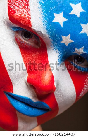 Close up of woman painted face. United States of America is painted on the face