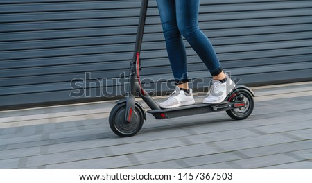 Close up of woman riding black electric kick scooter at cityscape, motion blur #1457367503