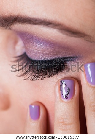 Close-up Of Woman's Eye With Purple Eyeshadow And Finger Nail Varnish