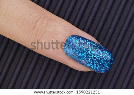 Close up of woman's finger with glitter fingernail polish