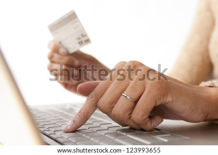 Close up of woman's fingers on computer keyboard while holding credit card