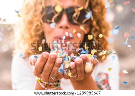 Close up of woman's habd and beautiful lady blowing out coloured carnival party confetti - focus on colors papers and hapiness and joyful lifestyle concept for happy people outdoor #1289985667