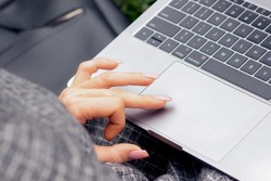 Close up of woman's hand and finger using touchpad of laptop. Female hand is using a touchpad on a laptop close up. Lifestyle and technology concept.