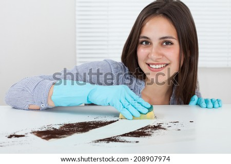 Close-up of woman\'s hand cleaning dirt on table with sponge at home