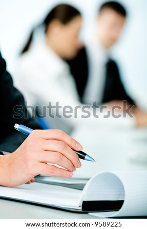 Close-up of woman's hand holding a pen on the background of people