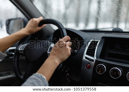 Close-up of woman's hand holding a steering wheel. Girl driver rides behind the wheel of a large car or SUV. #1051379558
