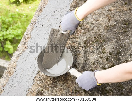 Close-up of woman's hand holding a trowel, applying mortar