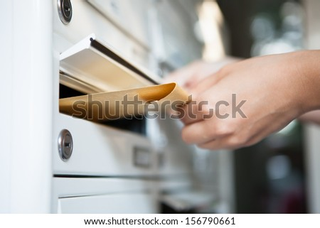 Close-Up Of Woman\'S Hand Holding Envelope And Inserting In Mailbox