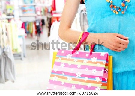 Close-up of woman?s hand holding paper bag while going shopping in the mall