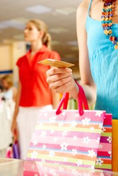 Close-up of woman?s hand holding plastic card while going shopping in the mall