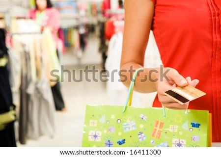 Close-up of womanâ??s hand holding plastic card while going shopping in the mall
