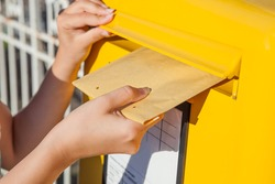 Close-up of woman's hand inserting envelope in mailbox