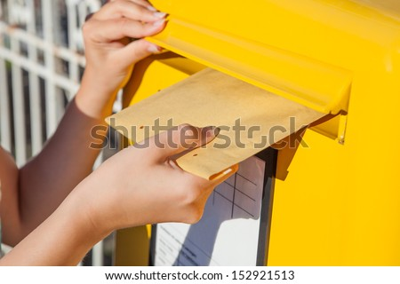 Close-Up Of Woman\'S Hand Inserting Envelope In Mailbox