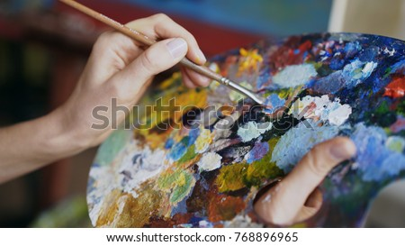 Close up of woman's hand mix paints with brush in palette in art-class
