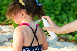 Close-up Of Woman's Hand Spraying Lotion On Her Daughter's Back