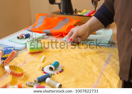 Close-up of woman's hand stitching quilting. Tailor Woman working in his tailor shop, Tailoring. Garment industry, tailoring concept #1007822731