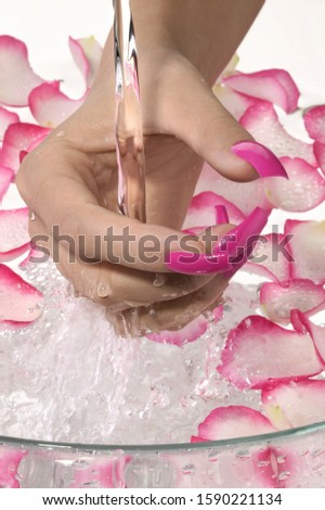 Close up of woman's hand with artificial fingernails in bowl of water and flower petals