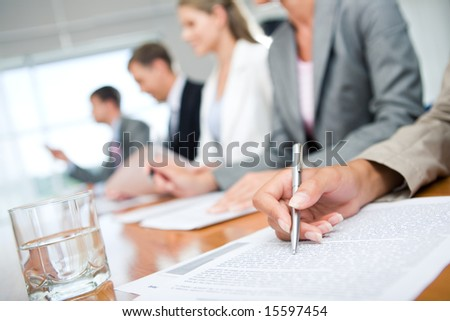 Close-up of womanâ??s hand with pen over document on background of business group
