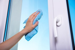 close up of woman's hand with special rag cleaning window